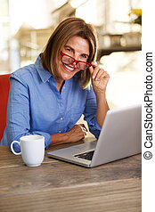 business woman smiling at table and working with laptop computer