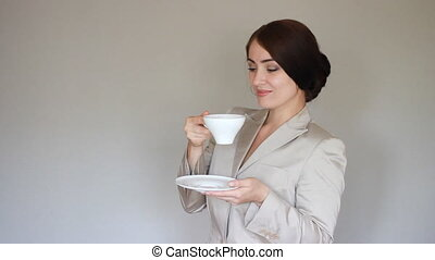 Business woman smiling, looking at camera and drinking coffee. Break