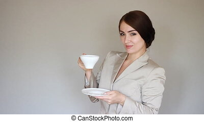 Business woman smiling, looking at camera and drinking coffee. or tea. Break. Young woman winks.
