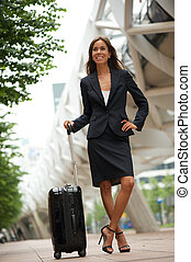Business woman smiling with suitcase in the city
