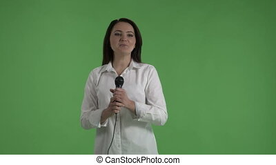Business woman speaking into microphone in front of audience at presentation