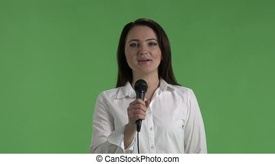 Business woman speaking into microphone looking directly at the camera