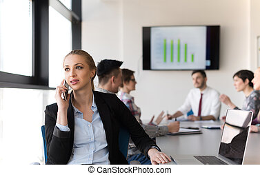 business woman speeking on phone at office with team on meeting in background