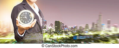 Business woman Stand and hold a magic ball with clock on abstract night time and building.