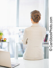 Business woman standing in office. rear view