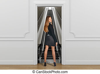 Business woman standing in the doorway going on escalator