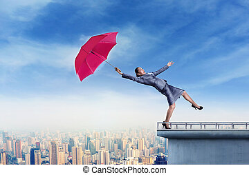 Business woman standing on the edge with umbrella