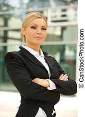 Business woman standing outdoors with arms crossed
