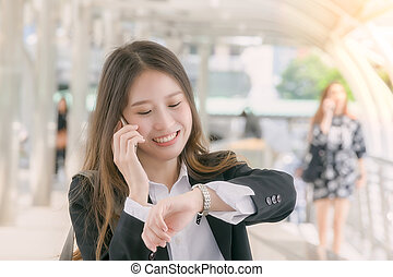 Business woman talk to smart phone andwatching wrist watch on the walk way :business outside concept