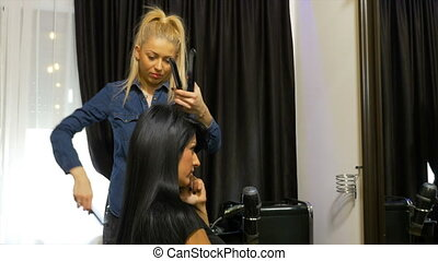 Business woman talking at the mobile phone while getting a hairdo at beauty salon