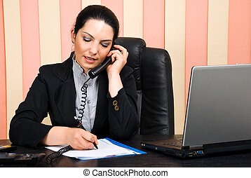 Business woman talking by phone and write on paper