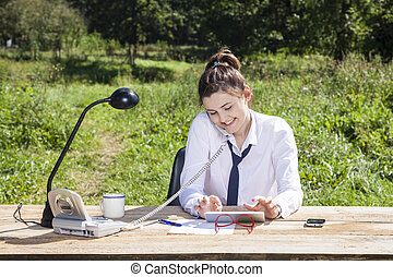 business woman talking on the phone and writes something