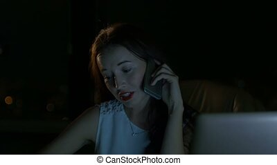 Business woman talking on the phone in the dark