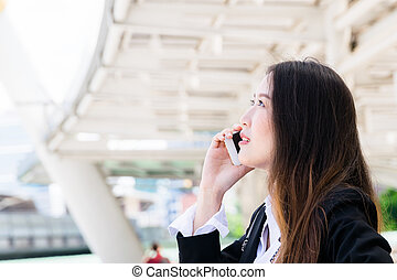 Business woman talking on the phone on her way to the office:business outside concept