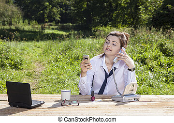 business woman talking on the phone, the other holds in her hand