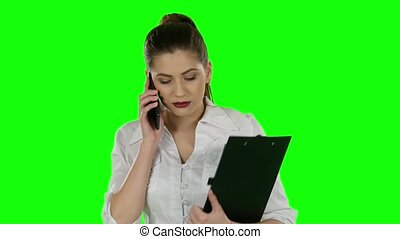 Business woman talking on the phone with folder in hands. Green screen