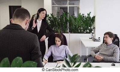 Business woman talking to her colleagues at workplace in office