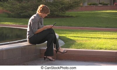 Business woman texting by a fountain