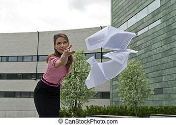 business woman throwing papers in the camera