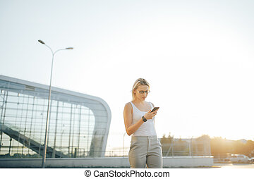 Business woman using a phone and clock while standing in outdoor