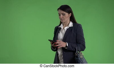 Business woman waiting for taxi talking on the phone against green screen