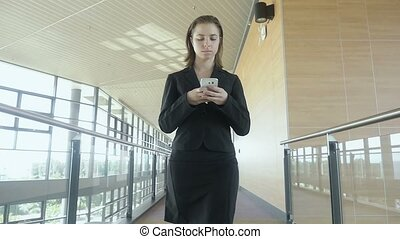 Business woman walking and texting in office