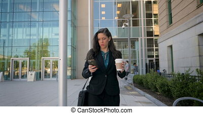 Business woman walking and texting on smartphone with a to go coffee cup in 4k