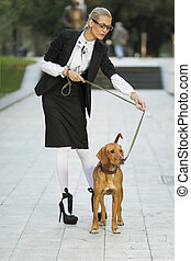 Business woman walking with a hound dog