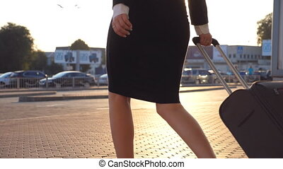 Business woman walking with her suitcase from airport hall...
