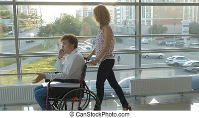 Business woman wheeling a wheelchair with a disabled businessman on a wheelchair who is talking on the phone