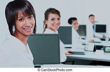 Business woman with a computer at the office with a group behind.