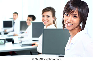 Business woman with a computer at the office with a group behind