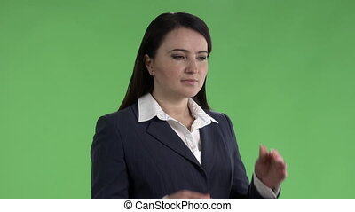 Business woman with a headache holding head against a green screen.
