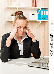 Business woman with a headache looking at the laptop in the office