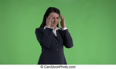Business woman with a headache massaging her temples against a green screen