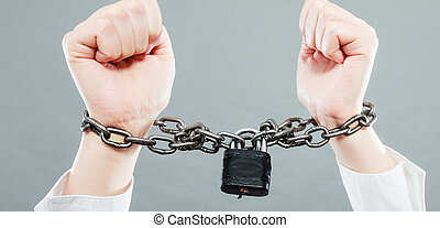 Crime, arrest jail or business concept. Closeup woman with chained hands on grunge background