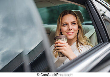 Business woman with coffee sitting on back seats in taxi car.