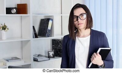 Business woman with folder stands in the office