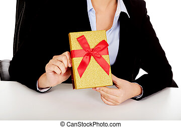 Business woman with gift box sitting behind the desk