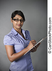 Business Woman with glasses writing on clipboard