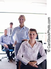 business woman with her staff in background at office
