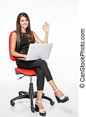 Business woman with laptop gesturing OK