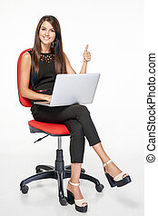 Business woman with laptop gesturing thumb up