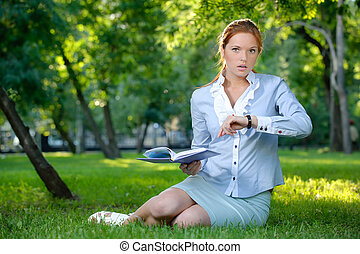 Business woman with notebook looking on her clock