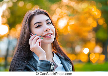 Business woman with smartphone close up in autumn park in sunset light. Girl have conversation with cell phone. Beautiful caucasian young woman talking with mobile device