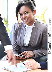 Business woman woking with a tablet in her hands, her co-workers discussing business matters in the background, tilt up