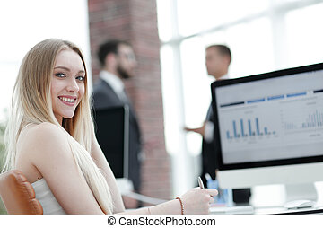 Business woman working in office with business graph on computer