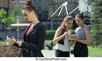 Business woman working on a tablet on the background of their business partners