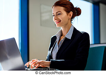 Business woman working on laptop in the office.
