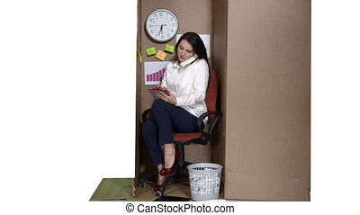 Business woman working on tablet computer inside cardboard box small office